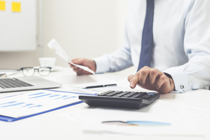 Geschäftsmann vergleicht mit Hilfe von Unterlagen und einem Taschenrechner Depots